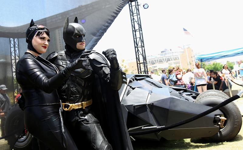 """Comic-Con attendees Katie Mitchell, left, and Jonathan Graves, from Los Angeles, strike a pose in front of the Tumbler Batmobile """"Batman Begins"""" and """"The Dark Knight"""" during Comic-Con, Saturday, July 14, 2012, in San Diego. (Photo by Matt Sayles/Invision/AP)"""