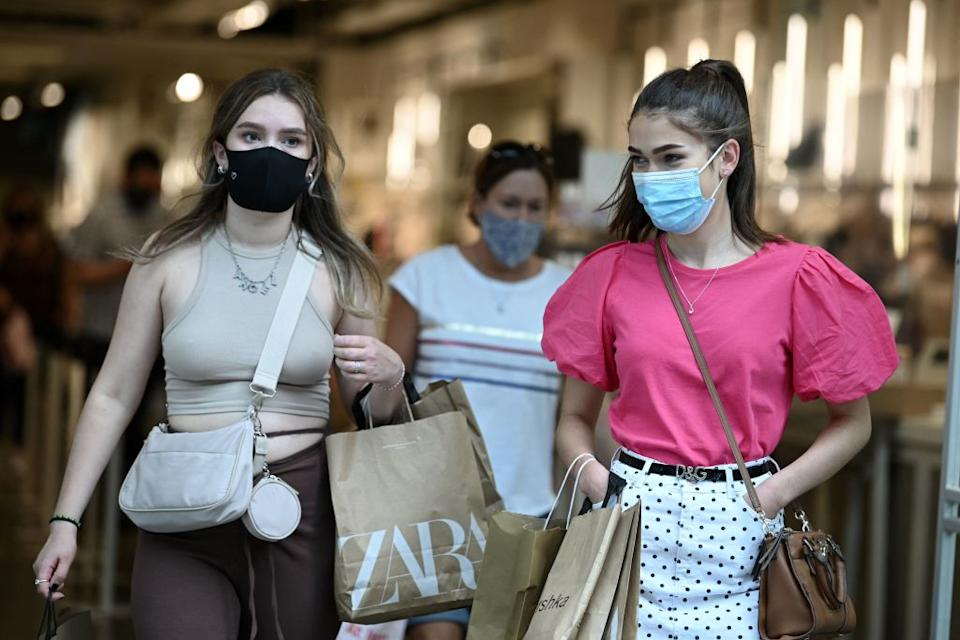 Shoppers wearing coronavirus face masks leave a store on Oxford Street in central London.