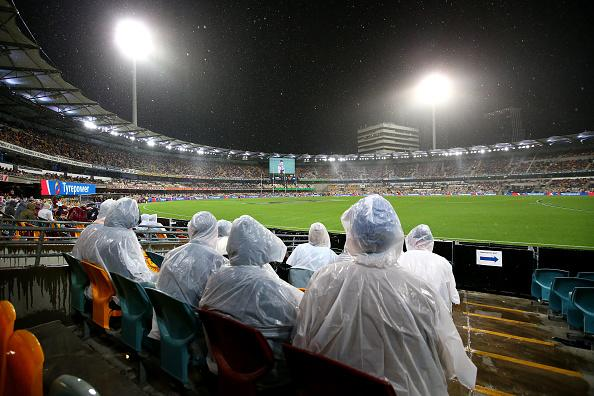 Rain falls on the crowd during AFL match at The Gabba.