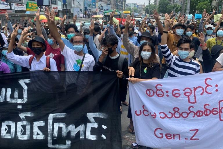 Protesters hold up the three-finger salute in an anti-junta demonstration in Yangon