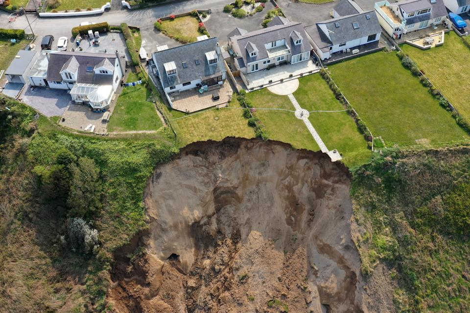 NEFYN, WALES - APRIL 21: Houses are seen next to the cliff edge after a landslide at Nefyn Beach in Gwynedd, North Wales on April 21, 2021 in Nefyn, United Kingdom. Following the large land slip people were advised to temporarily relocate. (Photo by Christopher Furlong/Getty Images)