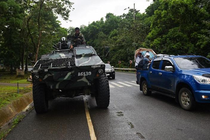 Thousands of residents have fled Marawi, gathering their belongings and heading onto a highway where Armoured Personnel Carriers (APCs) also patrolled (AFP Photo/TED ALJIBE)