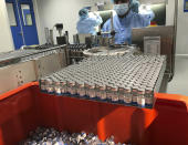 Production personnel perform the labeling operation of inspected vaccine vials inside the Incepta plant on the outskirts of Dhaka in Bangladesh Saturday Feb. 13, 2021. (AP Photo/Al-emrun Garjon)
