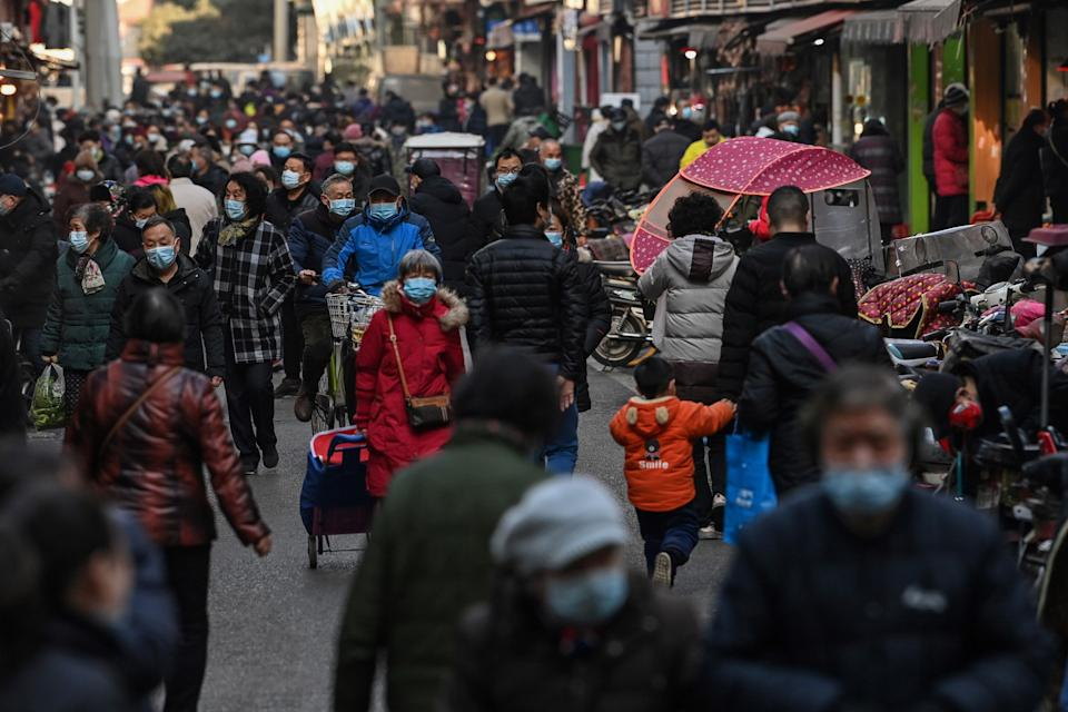 <p>People walk along a street near a market in Wuhan, China's central Hubei province on 19 January, 2021.</p> (AFP via Getty Images)