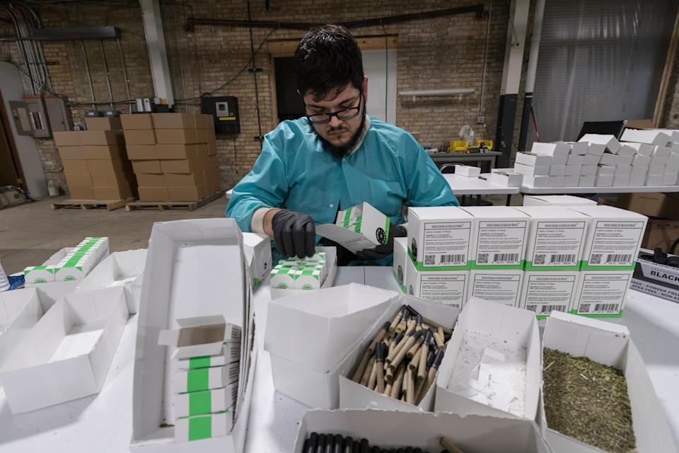 A worker packages hemp cigarettes at Vance Global.