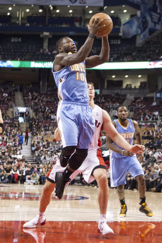 Denver Nuggets' Nate Robinson, left, goes up for a basket as Toronto Raptors' Tyler Hansbrough look on during the second half of an NBA basketball game on Sunday, Dec. 1, 2013, in Toronto. (AP Photo/The Canadian Press, Chris Young)