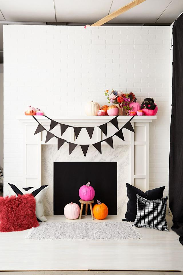 <p>Put vibrant pumpkins in pink and orange on full display, and finish the look with a playful black pennant banner. </p>