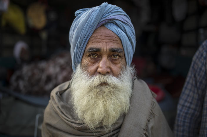 """Jagtar Singh, 78, sits for a photograph on the back of his tractor trolley parked on a highway as he joins other farmers protesting against new laws they say will result in their exploitation by corporations, eventually rendering them landless, at the Delhi-Haryana state border, India, Tuesday, Dec. 1, 2020. Instead of cars, the normally busy highway that connects most northern Indian towns to the capital is filled with tens of thousands of protesting farmers, many wearing colorful turbans. Their convoy of trucks, trailers and tractors stretches for at least three kilometers (1.8 miles) in a siege of sorts and the mood among the protesting farmers is boisterous. Their rallying call is """"Inquilab Zindabad"""" (""""Long live the revolution"""").(AP Photo/Altaf Qadri)"""