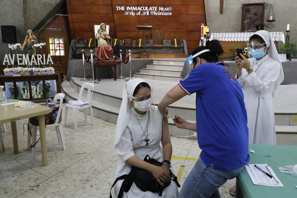A Catholic nun is inoculated with AstraZeneca COVID-19 vaccine at the Immaculate Heart of Mary Parish Church that turned into a temporary vaccination center in Quezon City, Philippines on Friday, May 21, 2021. Philippine officials have been ordered not to disclose in advance the COVID-19 vaccine brands to be administered in immunization sites after those offering newly arrived Pfizer shots drew big crowds in what could be an indication of public preference for Western vaccines. (AP Photo/Aaron Favila)