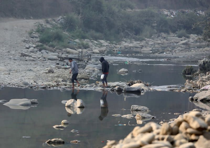 FILE PHOTO: People cross the Tiau river which marks the India-Myanmar border at Zokhawthar village