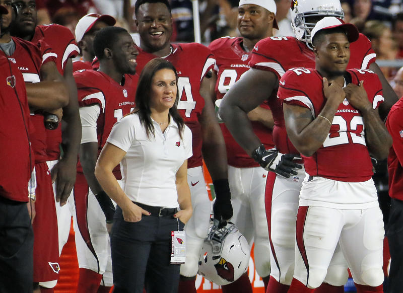 FILE - In this Aug. 22, 2015, file photo, Arizona Cardinals training camp coach Jen Welter watches from the sidelines during the second half of an NFL game against the San Diego Chargers in Glendale, Ariz. Praising the coaches and players for accepting her without reservation, Jen Welker is proud she's opened another door for women in men's professional sports as the first female coach of any kind on an NFL team. (AP Photo/Matt York, File)