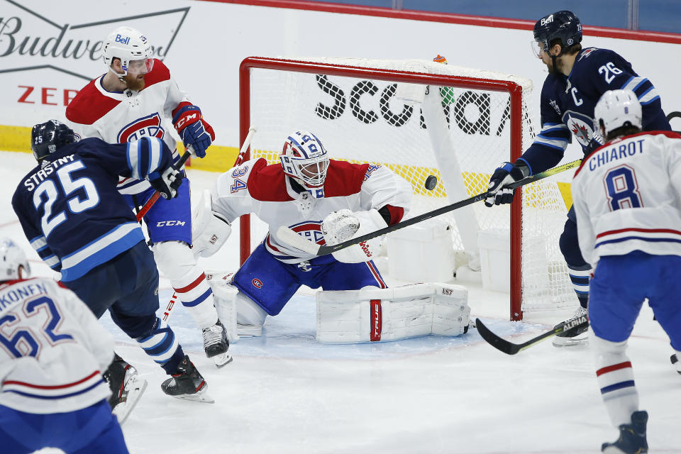 Montreal Canadiens goaltender Jake Allen (34) makes a save as Winnipeg Jets' Blake Wheeler (26) attempts to tip in the rebound during the second period of an NHL hockey game Saturday, Feb. 27, 2021, in Winnipeg, Manitoba. (John Woods/The Canadian Press via AP)