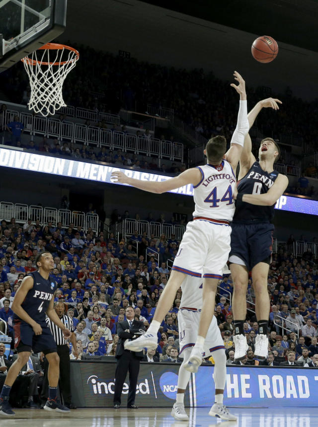 Pennsylvania forward Max Rothschild (0) shoots as Kansas forward Mitch Lightfoot (44) defends during the first half of an NCAA college basketball tournament first-round game Thursday, March 15, 2018, in Wichita, Kan. (AP Photo/Charlie Riedel)