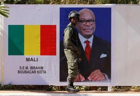 A Malian soldier stands guard next to Malian President Ibrahim Boubacar Keita's portrait at the international conference center of Bamako ahead of France-Africa summit in Bamako