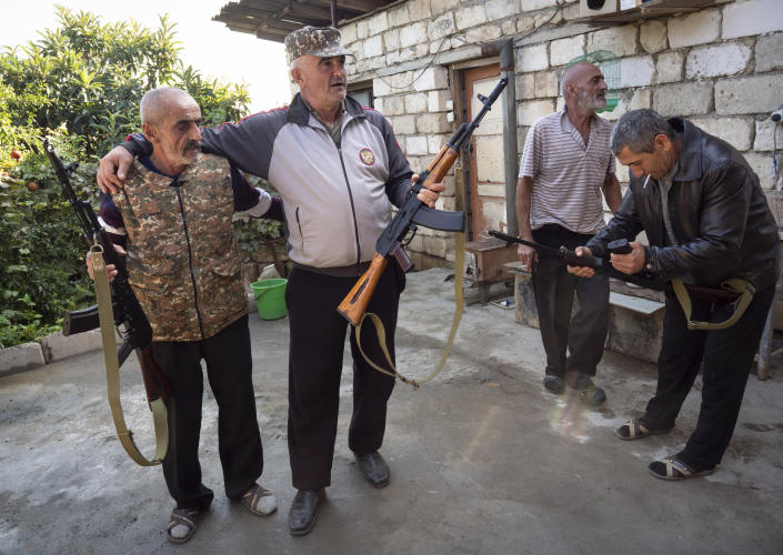 Local residents hold Kalashnikov guns that they received from a recruitment office in the town of Martuni, the separatist region of Nagorno-Karabakh, Wednesday, Oct. 14, 2020. The conflict between Armenia and Azerbaijan is escalating, with both sides exchanging accusations and claims of attacks over the separatist territory of Nagorno-Karabakh. Heavy fighting is in a third week despite a cease-fire deal. (AP Photo)