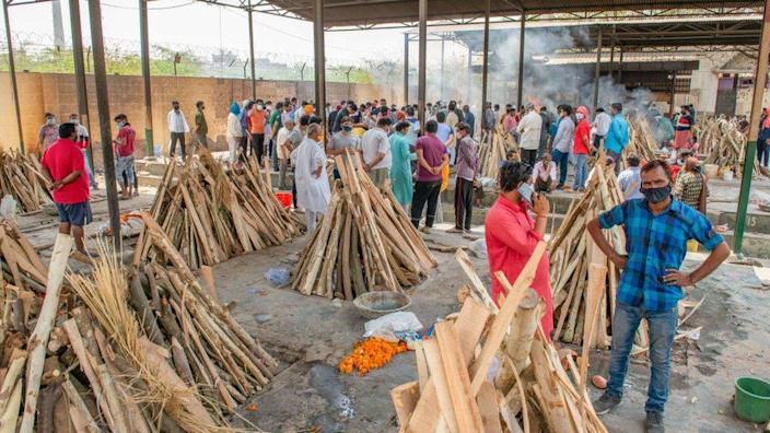 People perform the last rites for relatives who died of Covid-19 disease as other funeral pyres are seen during a mass cremation at Ghaziapur Municipal crematorium.