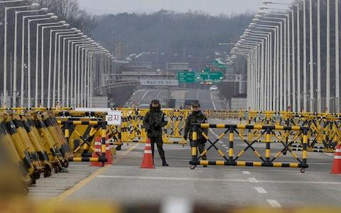 South Korean army soldiers stand guard on Unification Bridge, which leads to the demilitarized zone, near the border village of Panmunjom in Paju, South Korea - Credit: Ahn Young-joon/AP