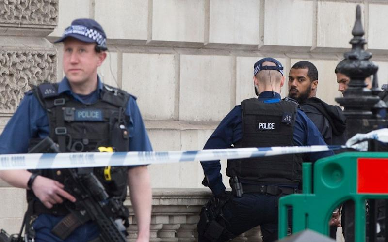 Armed police stand guard following the arrest - Credit:  Heathcliff O'Malley