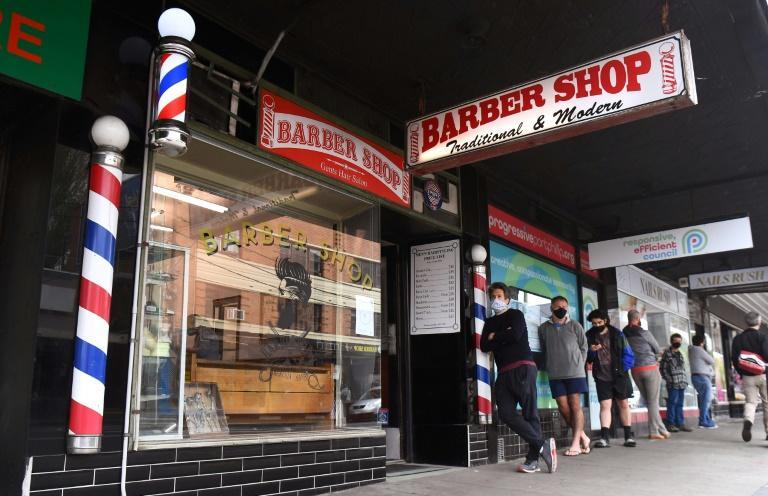 Men queue for a haircut outside a barber shop in Melbourne on October 19, 2020, as restrictions ease on falling infection rates.