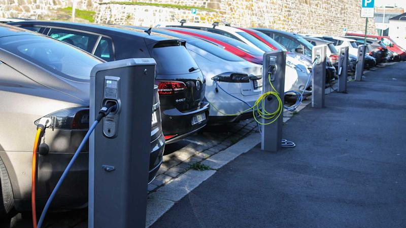Electric cars plugged in and charging at a car park on the street in Oslo Norway