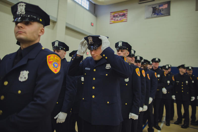 Matias Ferreira, center, adjusts his hat during his graduation ceremony from the Suffolk County Police Department Academy at the Health, Sports and Education Center in Suffolk, Long Island, New York, Friday, March 24, 2017. Ferreira, a former U.S. Marine Corps lance corporal who lost his legs below the knee when he stepped on a hidden explosive in Afghanistan in 2011, is joining a suburban New York police department. The 28-year-old graduated Friday from the Suffolk County Police Academy on Long Island following 29 weeks of training. (AP Photo/Andres Kudacki)