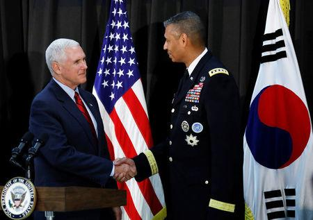 U.S. Vice President Mike Pence shakes hands with commander General Vincent K. Brooks during an Easter fellowship dinner at a military base in Seoul, South Korea, April 16, 2017.  REUTERS/Kim Hong-Ji