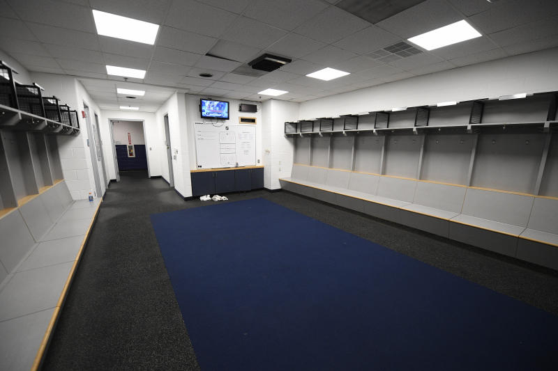The empty visitors NHL hockey locker room is seen at Capital One Arena in Washington, Thursday, March 12, 2020. The Washington Capitals were to play the Detroit Red Wings later tonight. The NHL is following the NBA's lead and suspending its season because of the coronavirus pandemic. NHL Commissioner Gary Bettman announced Thursday it is pausing its season, one day after the NBA suspended play after a player tested positive Wednesday for COVID-19.(AP Photo/Nick Wass)