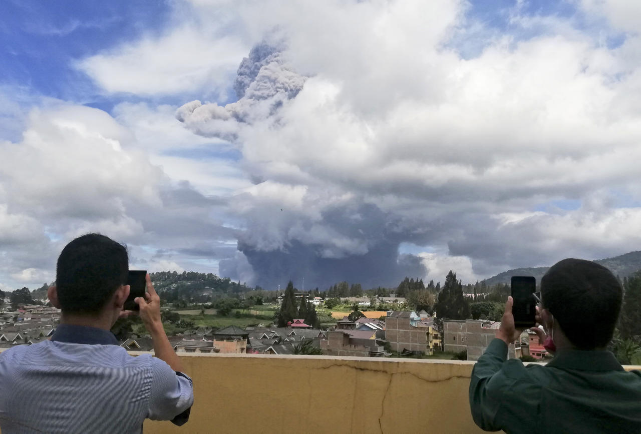 """Indonesian men use their mobile phones to take photos as Mount Sinabung spews volcanic materials into the air as it erupts, in Karo, North Sumatra, Indonesia, Monday, Aug. 10, 2020. The rumbling volcano erupted Monday, sending a column of volcanic materials a few thousands meters into the sky. Sinabung is among more than 120 active volcanoes in Indonesia, which is prone to seismic upheaval due to its location on the Pacific """"Ring of Fire,"""" an arc of volcanoes and fault lines encircling the Pacific Basin. (AP Photo/Sugeng Nuryono)"""