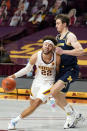 Minnesota's Gabe Kalscheur (22) drives around Michigan's Franz Wagner (21) in the first half of an NCAA college basketball game, Saturday, Jan. 16, 2021, in Minneapolis. (AP Photo/Jim Mone)