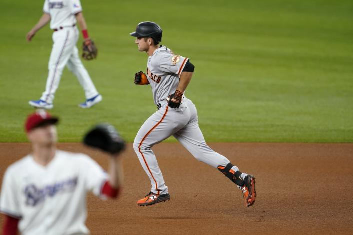 San Francisco Giants' Jason Vosler, right, rounds the bases after hitting a solo home run off of Texas Rangers' Kyle Gibson, left front, in the fifth inning of a baseball game in Arlington, Texas, Wednesday, June 9, 2021. (AP Photo/Tony Gutierrez)