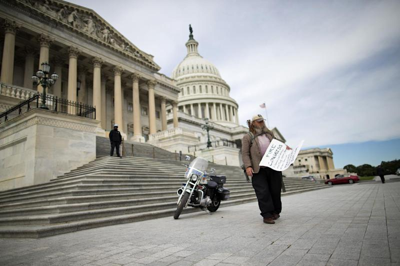 """FILE - In this Oct. 8, 2013, file photo, Rick Hohensee of Washington holds a """"Fire Congress"""" sign near the House steps on Capitol Hill in Washington. A new poll says Americans are holding Republicans primarily responsible for the partial government shutdown. The Associated Press-GfK survey finds plenty of disdain to go around as people size up the federal impasse. Most now disapprove of the way President Barack Obama is handling his job, and Congress' approval rating is a perilous 5 percent. (AP Photo/ Evan Vucci)"""