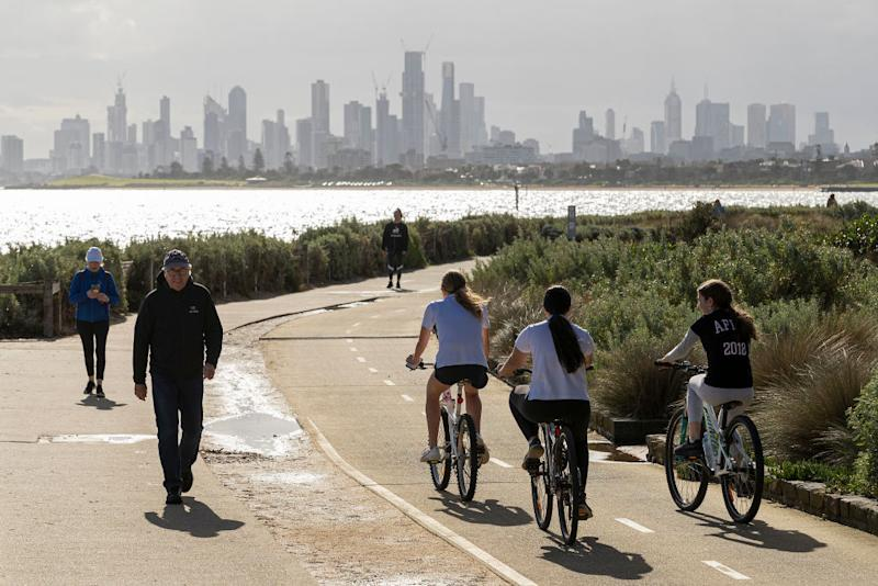 People walk and ride along the beach at Brighton in Melbourne, Australia.