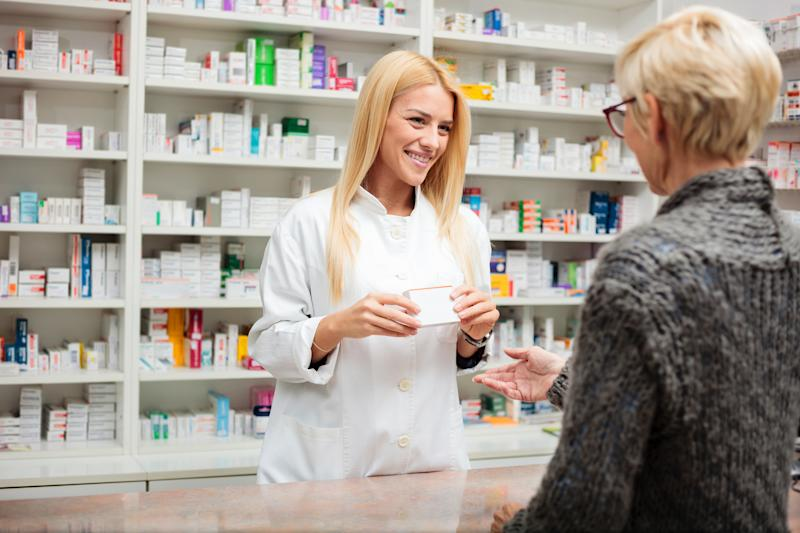 Pharmacist speaking with client about prescription at pharmacy counter