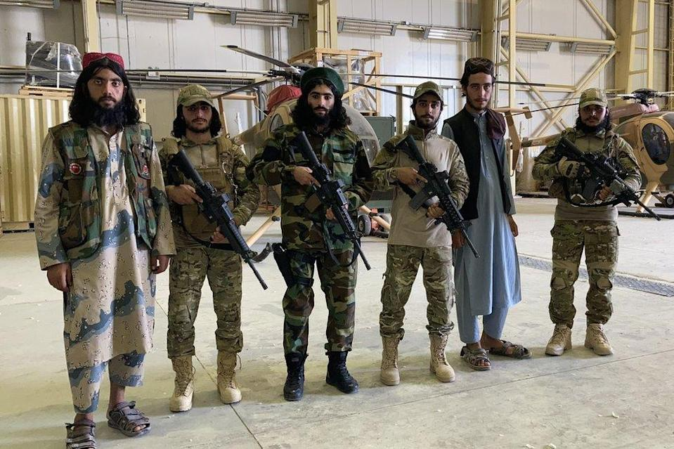 Taliban fighters pose in front of former army helicopters at Balkh airfield.