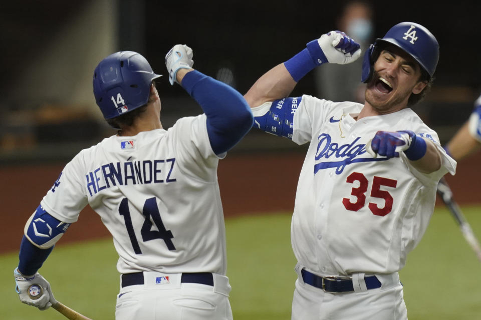 Los Angeles Dodgers' Cody Bellinger, right, celebrates his home run with Enrique Hernandez against the Atlanta Braves during the seventh inning in Game 7 of a baseball National League Championship Series Sunday, Oct. 18, 2020, in Arlington, Texas.(AP Photo/Eric Gay)