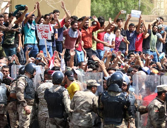 Iraqi riot police line up as protesters chant slogans and hold up signs during a demonstration in Basra on July 15, 2018 (AFP Photo/Haidar MOHAMMED ALI)