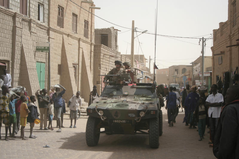 French soldiers are watched by local people, as they drive through the city streets of Timbuktu, Mali, Thursday Jan. 31, 2013. Many things have changed in Timbuktu since the Islamic militants ceased to enforce their law and relinquished power to French special forces who parachuted in several days ago, liberating this storied city, and now there is a growing sense of freedom. (AP Photo/Harouna Traore)