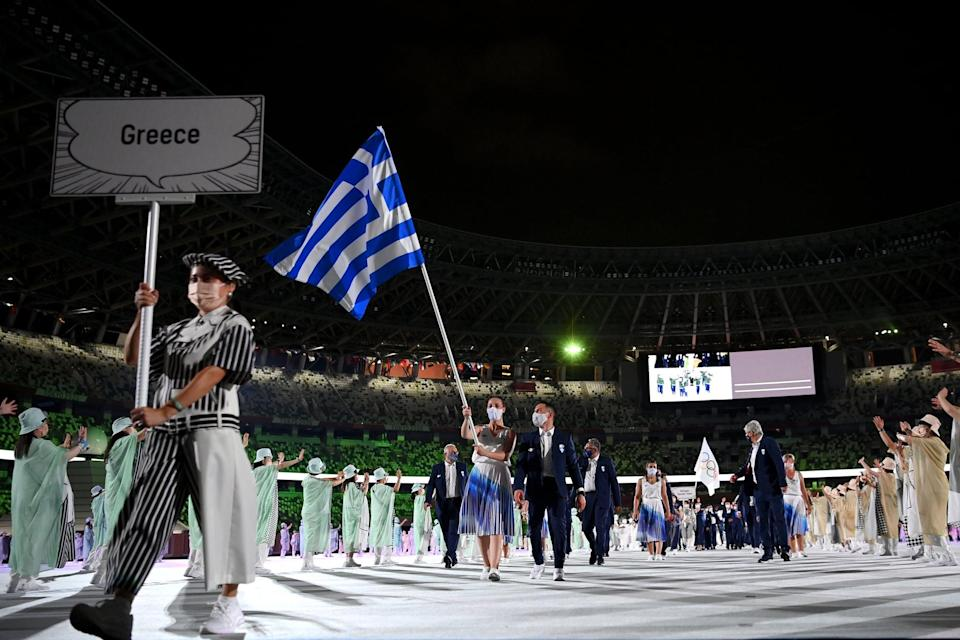 TOKYO, JAPAN - JULY 23: Flag bearers Anna Korakaki and Eleftherios Petrounias of Team Greece lead their team in during the Opening Ceremony of the Tokyo 2020 Olympic Games at Olympic Stadium on July 23, 2021 in Tokyo, Japan. (Photo by Matthias Hangst/Getty Images)