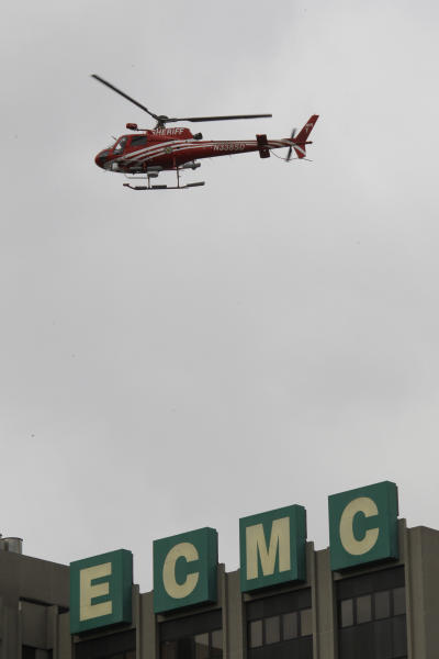 "An Erie County Sheriff's helicopter searches at the scene of a shooting at Erie Count Medical Center in Buffalo, N.Y., Wednesday, June 13, 2012. A police official confirms that a woman was killed Wednesday morning on the grounds of the Erie County Medical Center, which he describes as being in ""complete lockdown"" as SWAT teams and other officers cordon off the 65-acre campus. (AP Photo/David Duprey)"