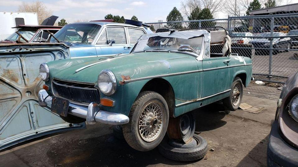 """<p>The tiny <a href=""""https://en.wikipedia.org/wiki/MG_Midget"""" rel=""""nofollow noopener"""" target=""""_blank"""" data-ylk=""""slk:MG Midget"""" class=""""link rapid-noclick-resp"""">MG Midget</a> (and its near-identical sibling, the Austin-Healey Sprite) sold well in North America during its 1961-1980 production run, because everyone likes a cheap and fun two-seat convertible. With the exception of the occasional super-original or nicely restored examples, though, the Midget never has been worth serious money, which means that thousands of these cars languish as get-to-it-someday projects in the driveways, yards, and garages of the land. In <a href=""""http://www.murileemartin.com/JunkyardGalleryHome.html"""" rel=""""nofollow noopener"""" target=""""_blank"""" data-ylk=""""slk:my junkyard travels"""" class=""""link rapid-noclick-resp"""">my junkyard travels</a>, I see <a href=""""http://www.murileemartin.com/Junkyard/JunkyardGallery-MG.html"""" rel=""""nofollow noopener"""" target=""""_blank"""" data-ylk=""""slk:the potential project Midgets"""" class=""""link rapid-noclick-resp"""">the potential project Midgets</a> that got swept into <a href=""""https://www.anrdoezrs.net/links/8980730/type/am/http://www.thetruthaboutcars.com/2011/03/end-of-the-line-welcome-to-the-crusher/"""" rel=""""nofollow noopener"""" target=""""_blank"""" data-ylk=""""slk:the crusher"""" class=""""link rapid-noclick-resp"""">the crusher</a>'s waiting room; most of them are mid-to-late-1970s models, but today's Junkyard Gem is a much older '67 model in a Denver-area yard. <a href=""""https://www.autoblog.com/2019/07/26/junkyard-gem-1967-mg-midget/"""" data-ylk=""""slk:Read more"""" class=""""link rapid-noclick-resp""""><em>Read more</em></a>.</p>"""