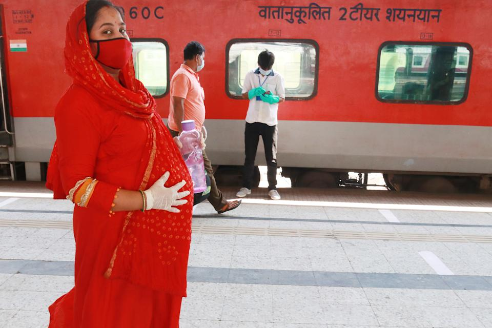 A pregnant women walk   to board a Special AC train for New Delhi after the government eased a nationwide lockdown imposed as a preventive measure against the COVID-19 coronavirus, Howrah rail station in Kolkata on May 12, 2020. (Photo by Debajyoti Chakraborty/NurPhoto via Getty Images)