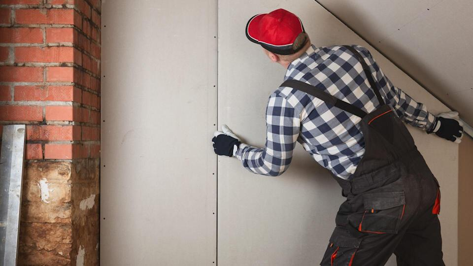 Man installing plasterboard sheet to wall for attic room construction.