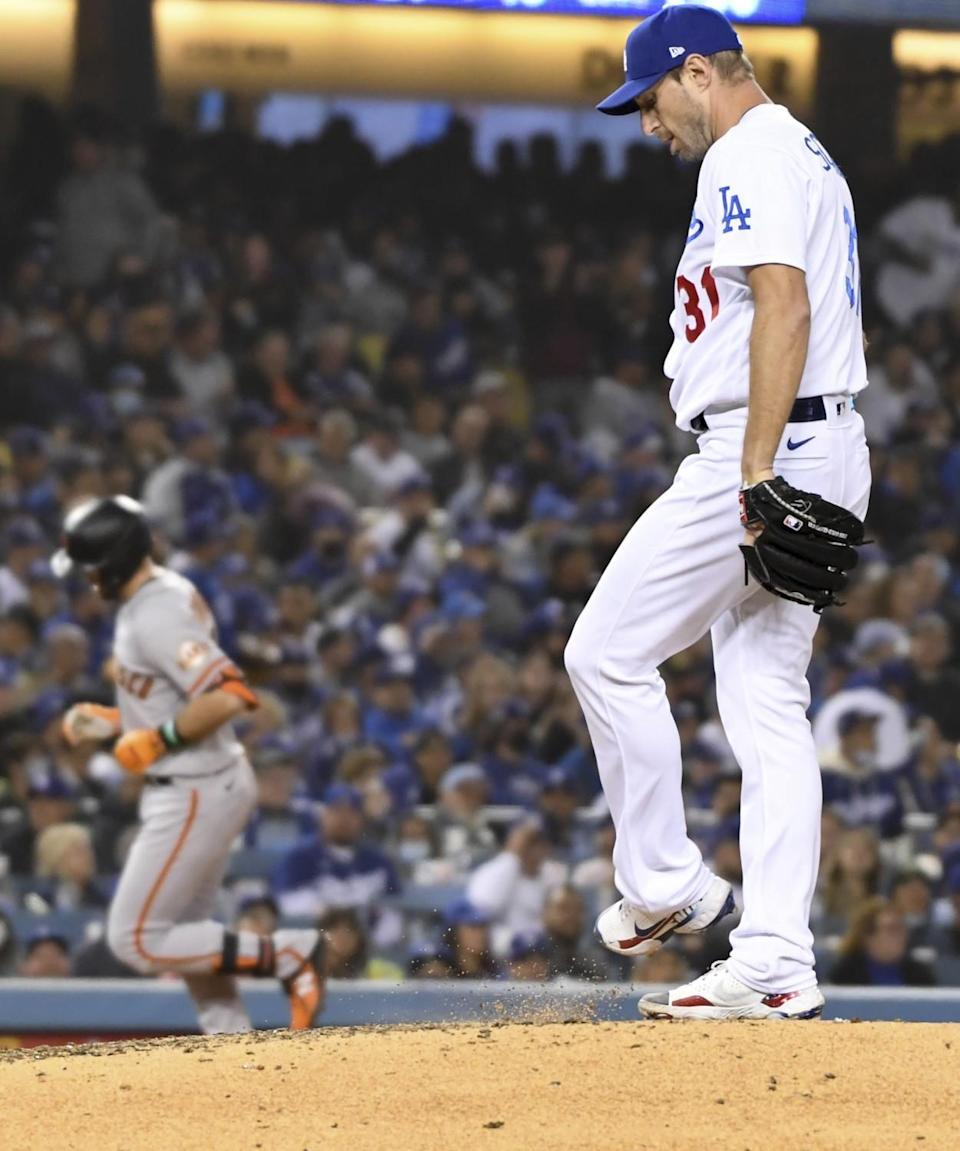 Dodgers starting pitcher Max Scherzer, right, kicks dirt off the mound as San Francisco's Evan Longoria rounds the bases.