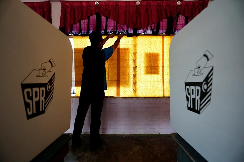 An election volunteer pastes sheets of paper on glass windows a day before the 14th general election at a polling station in Alor Setar May 8, 2018. — Reuters pic