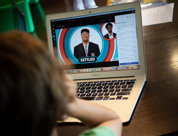 First grader Hawkes Powell pays attention to a lesson from his class on his laptop from his home on the first day of school Tuesday, Aug. 4, 2020 in Nashville, Tenn.