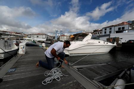 A man reinforces with ropes the mooring of his boat at a port before the arrival of Hurricane Lorenzo in Angra do Heroismo in the Azores islands