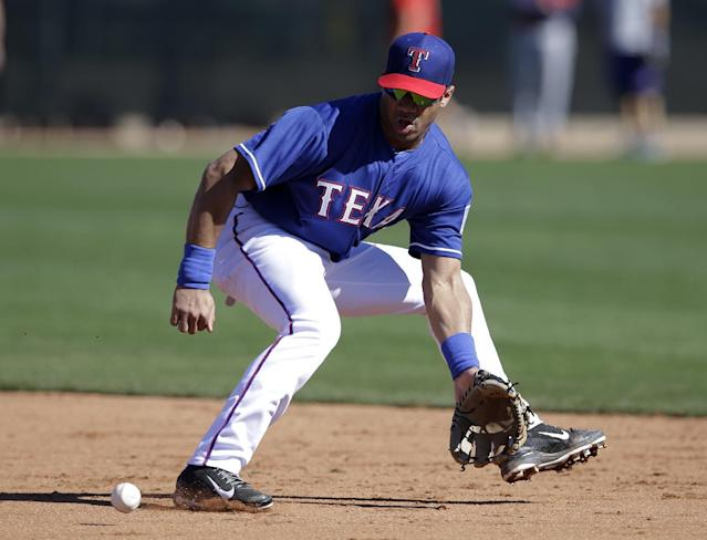 Seattle Seahawks quarterback Russell Wilson fields a ground ball at second while working out with the Texas Rangers during spring training baseball practice, Monday, March 3, 2014, in Surprise, Ariz. (AP Photo/Tony Gutierrez)
