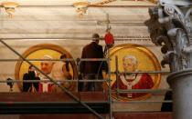 FILE PHOTO: Workers install a mosaic depicting Pope Francis next to the one depicting Pope Emeritus Benedict XVI at Saint Paul's Basilica in Rome