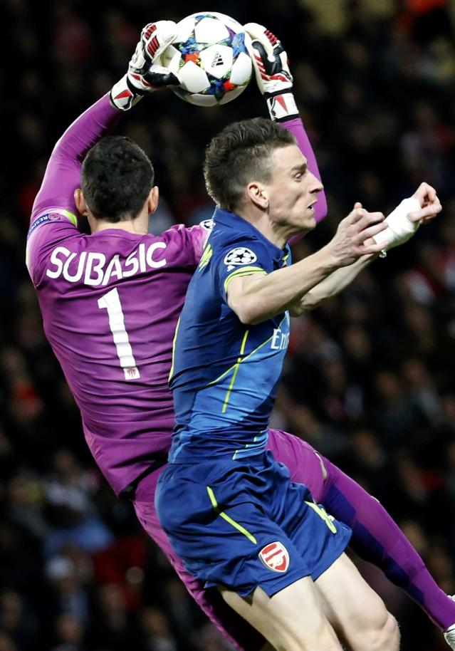AS Monaco's goalkeeper Danijel Subasic (L) grabs the ball as he jumps against Arsenal's Laurent Koscielny during their Champions League round of 16 second leg soccer match at the Louis II Stadium in Monaco, March 17, 2015. REUTERS/Eric Gaillard (MONACO - Tags: SPORT SOCCER)