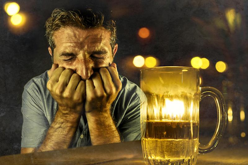 Cringing man next to mostly empty glass of beer